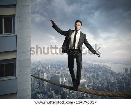 Equilibrist businessma on the rope - stock photo