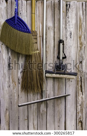 equipment hanging on the wooden wall ready for cleaning work. - stock photo