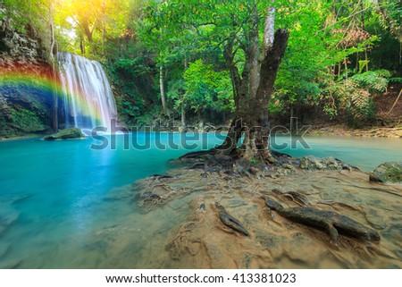 Erawan Waterfall, beautiful waterfall with sunlight rays in deep forest  - stock photo