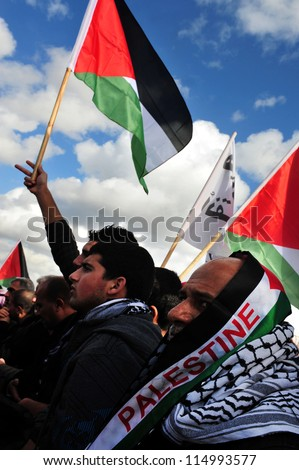 EREZ CROSSING-DECEMBER 31:Palestinian Arabs carry Palestinian flags during a protest on the Gaza-Israel border on Dec 31 2009.The entire  Palestinian population in Gaza Strip is 1.6 million people - stock photo