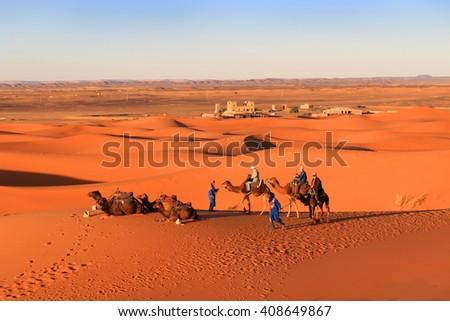 ERG CHEGGI, MOROCCO - FEBRUARY 28, 2016: People riding on a caravan of camels towards the dunes of the Sahara Desert at Erg Cheggi, Morocco at sunset - stock photo