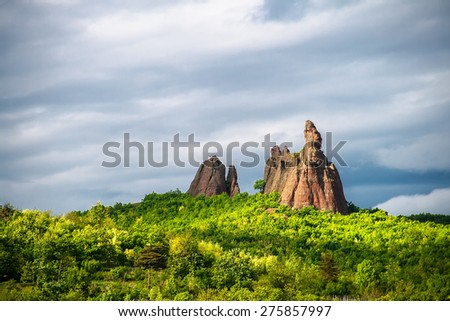 Eroded sand rock over green forest and dramatic sky background - stock photo