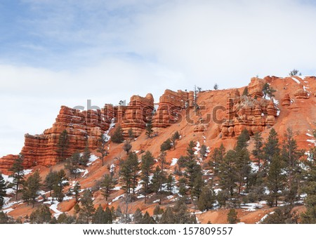 Erosion effecting the sandstone mountains and leaving towering pillars at the entrance of Red Canyon in Dixie National Park, Utah. - stock photo