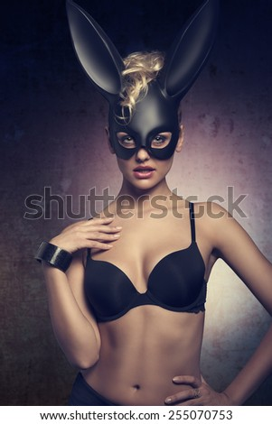 erotic easter dark portrait of very sexy blonde female with curly hair-style and black lingerie, wearing bizarre dark bunny mask on the face and looking in camera - stock photo