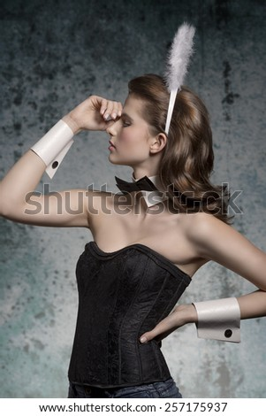 erotic easter portrait of young brunette girl in thoughtful pose with sexy corset and fluffy bunny ears  - stock photo