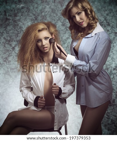 erotic portrait of two sexy girls with open shirt and creative hair-style applying blush and posing with naked legs  - stock photo