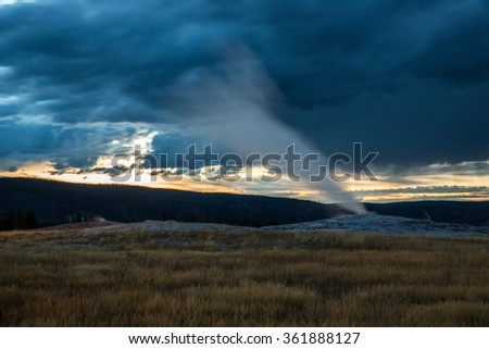Eruption of Old Faithful geyser at Yellowstone National Park during sunset hours.  - stock photo