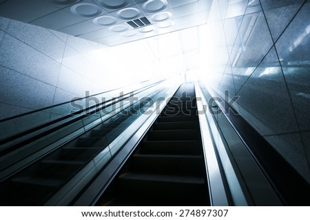 Escalator and light at end of tunnel - stock photo