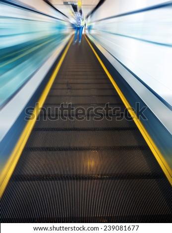 escalator leading forward, abstract motion blur - stock photo