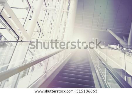 escalator leading to light. vintage filter. - stock photo