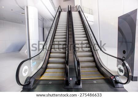escalator,Up and down escalators in public building. - stock photo