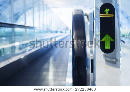 Escalator walkway with green Arrow sign symbol at Airport - stock photo