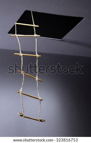 Escape concept. Rope ladder inside hatch in ceiling - stock photo