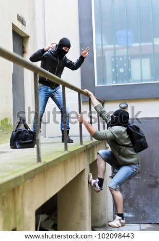 Escape from a robbery. One tries to help another to climb the rails. - stock photo