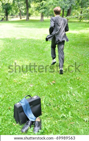 Escape from civilization concept - business man running in park away from bag, shoes and tie - stock photo