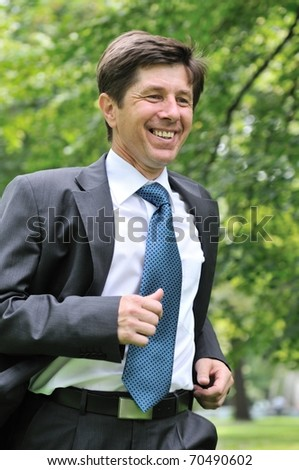 Escape from civilization - smiling senior business man running in park - stock photo