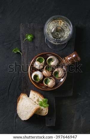Escargots de Bourgogne - Snails with herbs butter, in traditional ceramic pan with parsley, bread and glass of white wine on wooden chopping board over black textured background. Top view - stock photo