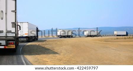 escort of trucks moves on mountain road - stock photo