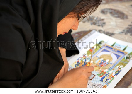 ESFAHAN, IRAN - DECEMBER 01, 2007: Muslim woman artist in black headscarf paints traditional Persian miniature - stock photo