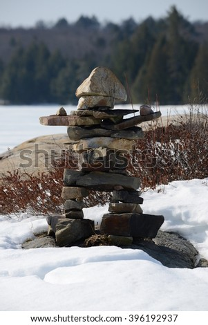 Eskimo Inuit rock man stone man on lake ice island. - stock photo