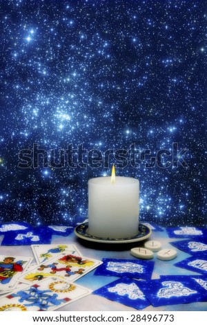 esoteric symbols like tarots cards, astrological symbols, runes and candle on a table - stock photo
