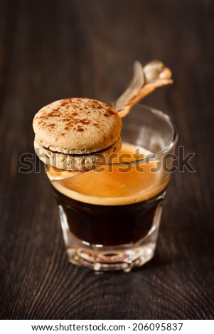 Espresso coffee and sweet chocolate macaron for breakfast. - stock photo