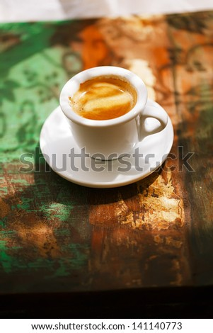 espresso coffee cup on rustic table with sun - stock photo