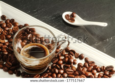 espresso coffee cup with coffee beans over ardesia - stock photo