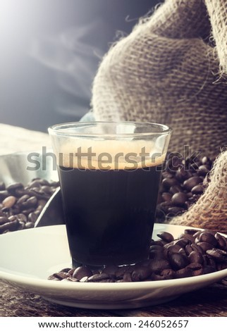 Espresso coffee in glass cup with coffee beans on wooden table. - stock photo