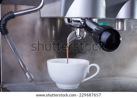 Espresso coffee machine, shot of espresso flowing into a cup. - stock photo