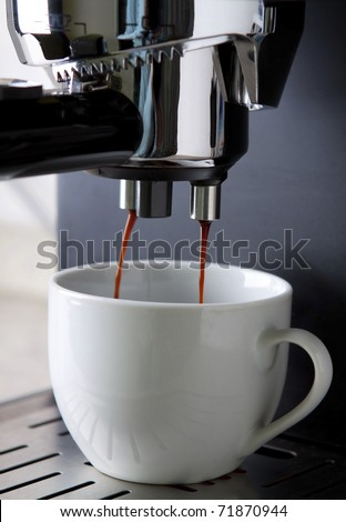 Espresso coffee maker in action with white cup - stock photo