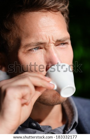 Espresso coffee - man drinking at cafe portrait. Handsome male drinking from espresso cup sitting outside at sidewalk cafe. Close up of male business man sitting outdoors in suit jacket. - stock photo