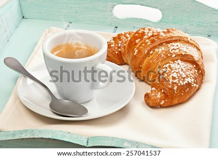 Espresso coffee with croissant in wooden tray light blue. - stock photo