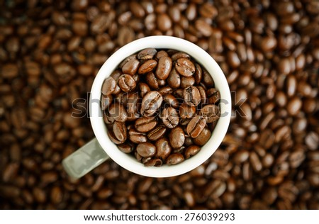 Espresso cup full of beans and a dark background of espresso beans. Shallow focus. - stock photo