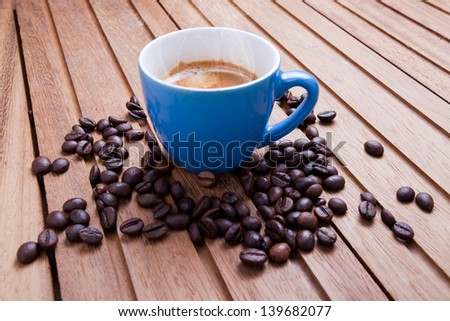 Espresso cup on wooden table with coffee beans - stock photo