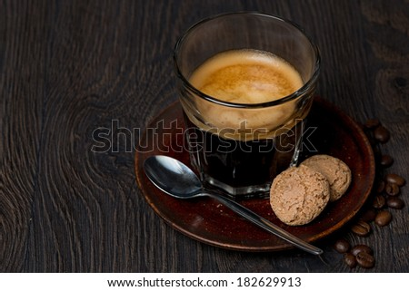 espresso in a glass and almond cookies on dark background, horizontal - stock photo