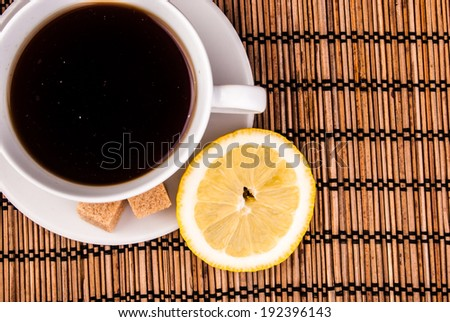 espresso in white cup with brown sugar and lemon on table covered with wooden mat - stock photo