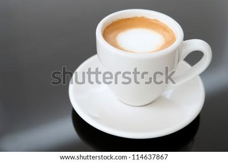 Espresso Macchiato in white cup with simple generic design on black glassy background - stock photo