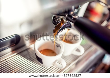 Espresso machine pouring fresh coffee into cups at restaurant. Coffee automatic machine making coffee - stock photo