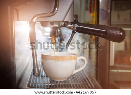 espresso machine with filter make coffee flowing into a cup. - stock photo