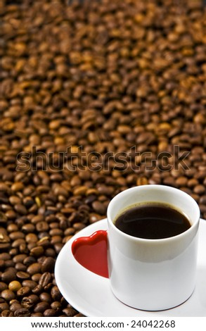 Espresso served on heart shaped cup on coffee beans - stock photo