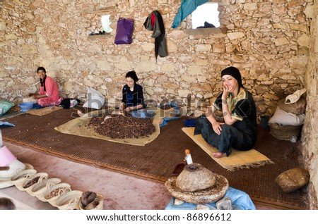 ESSAOUIRA, MOROCCO-AUGUST, 7: women working in a cooperative for the manufacturing of argan fruits in Essaouira, Morocco,  august 7, 2011. Only women work in these cooperatives - stock photo