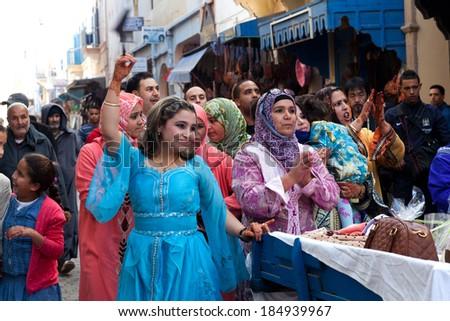 ESSAOUIRA, MOROCCO - 15 JANUARY 2014: Unidentified participants of traditional Muslim wedding ceremony dancing on the street on January 15, 2014 in Essaouira, Morocco. - stock photo