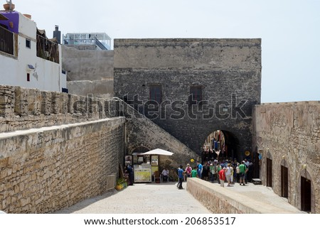 ESSAOUIRA, MOROCCO - MAY 14, 2014: Tourists arriving at historical landmark of fortress by the sea. Essaouira, Morocco. May 14, 2014.  - stock photo