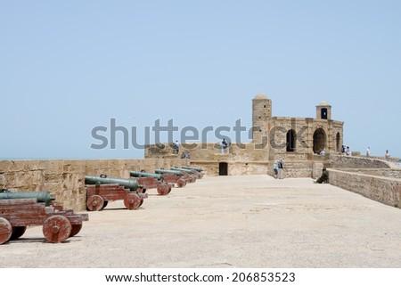 ESSAOUIRA, MOROCCO - May 14, 2014: Tourists walking and looking at historical fortress. Essaouira, Morocco. May 14, 2014. - stock photo