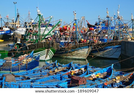 Essaouira port with blue boats for shark fishing and big ships at the morning. Morocco, the Atlantic coast, North Africa. The old town of Essaouira is the UNESCO world heritage. - stock photo