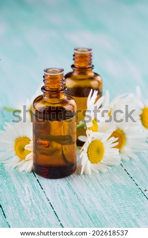 Essential aroma oil with chamomile on wooden background. Selective focus, vertical. - stock photo