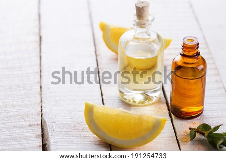 Essential aroma oil with lemon and mint  on wooden background. Selective focus, horizontal.  - stock photo