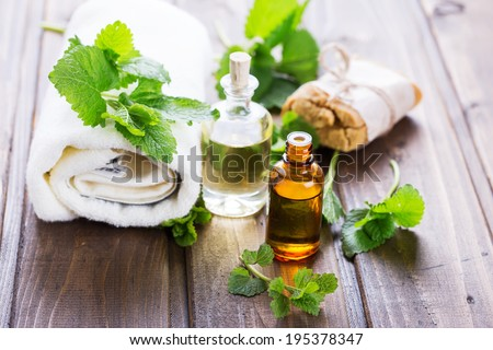 Essential aroma oil with melissa on wooden background. Selective focus, horizontal. - stock photo