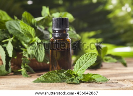 Essential aroma oil with peppermint on wooden background. Selective focus, horizontal. - stock photo
